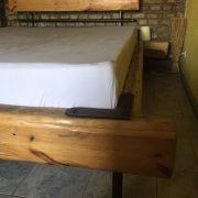 Bett aus Holz mit Metallstangen